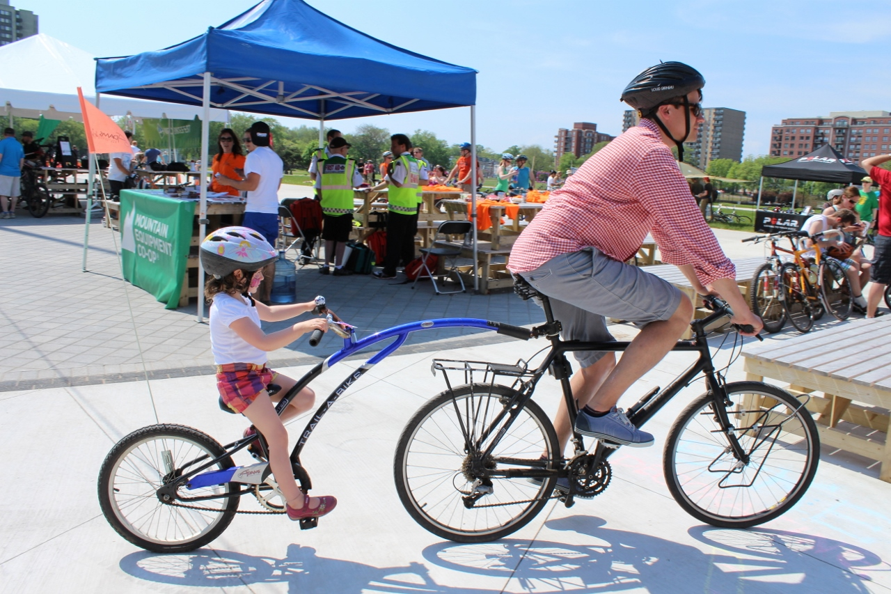 A man tows his daughter with his bike during Bike Fest 2012.